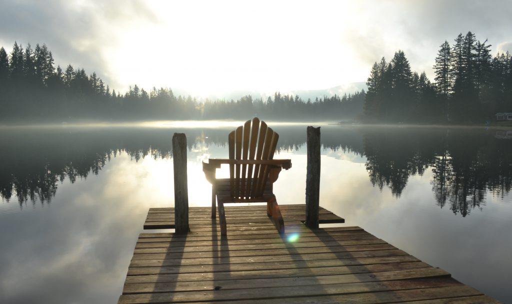 Deck chair on a dock on a foggy morniing