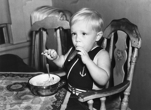 child smoking a cigar, sitting at a table in a high chair