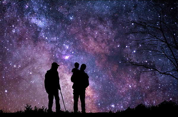 Three people staring at a star-filled night sky